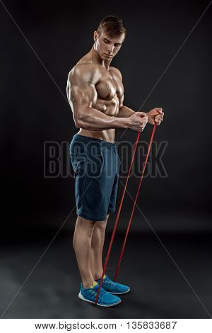 Young athletic man exercising and doing fitness with a chest expander, resistance band, on dark background