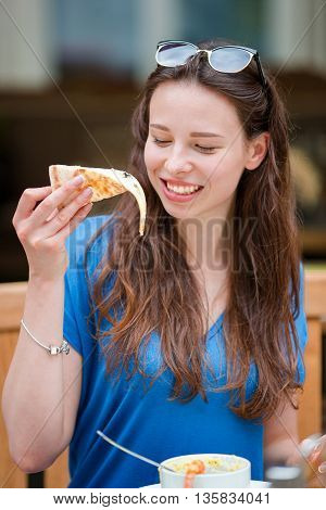 Portrait of cheerful young woman enjoying slice of pizza in the outdoor cafe
