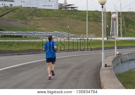 Man runs on the road along the waterfront of the Gulf in the city of Cheboksary Chuvash Republic Russia. 06/19/2016