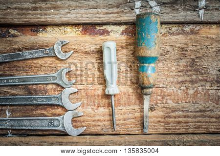 Old tools lie on the boards. Little old wrenches and screwdrivers.