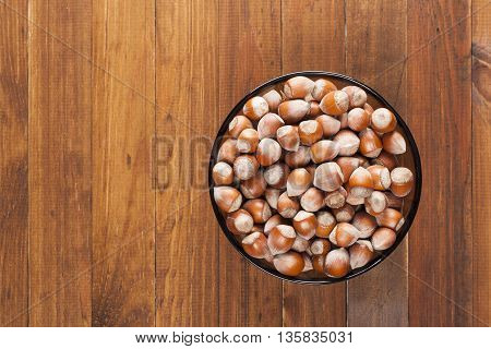 The crude hazelnut in translucent plate on the table with a wooden background with the top view plate Is located on the right. Healthy food.