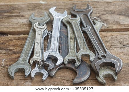 Set of old spanners lie on a wooden table. Close-up The old shop.