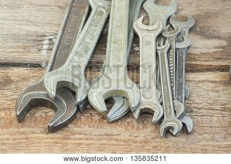 Set of old wrenches on clean wooden background. The old shop.