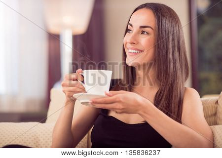 Coffee break. Close up of a charming woman holding a cup with hot coffee and looking aside while sitting in the living room