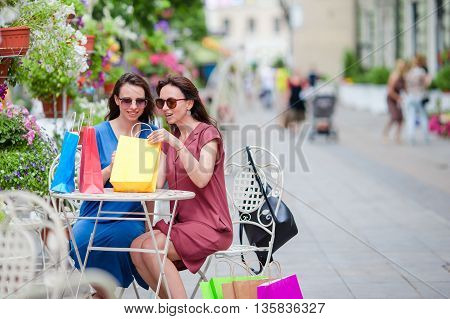 Two fashion colorful shoppers with bags shopping with a smart phone in the street