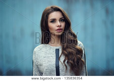 Calm or pensive girl portrait against blue old wooden wall. Pretty stylish fashionable woman in gray hoodie with long curly hair looking at you. Shallow DOF, blurred background
