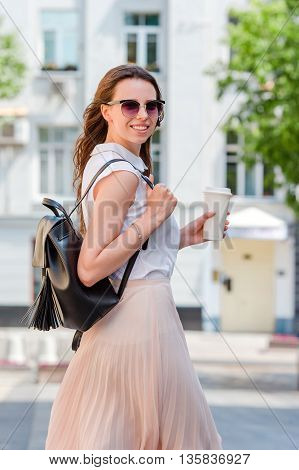 Girl caucasian drinking hot drink coffee walking in street at Europe
