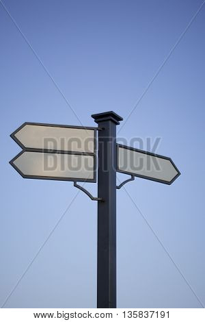 Signpost. Index path located on the pole. Black metal pole. Arrows with a white field for writing. Against the background of the blue sky.