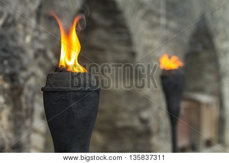 Ancient tower wall highlighted by pair of iron torch in Tallinn Old Town