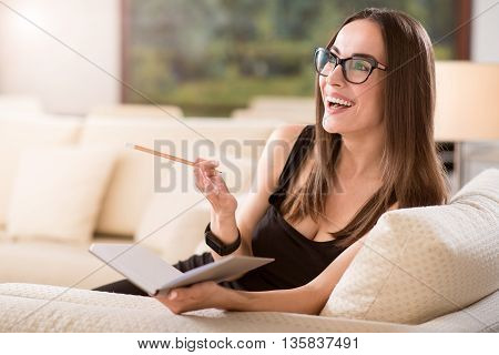 Look here. Cheerful surprised young woman sitting on the sofa and pointing with her hand in the open diary while looking aside