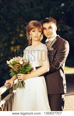 Beautiful caucasian just married couple posing in park and hugging. Beautiful vride in long white dress and groom in luxury costume
