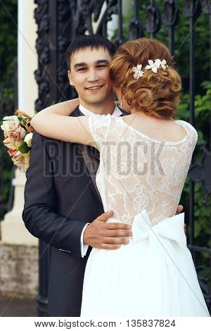 Bride in whire lace dress hugging her happy groom. View from girls back.
