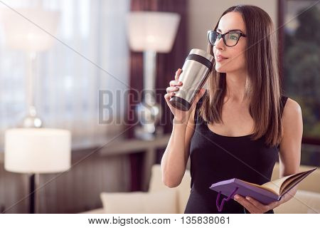 Coffee time. Charming beautiful young woman standing and dreaming while holding a thermo mug and an open notebook