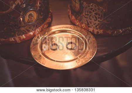 two plain golden wedding rings on a copper salver, orthodox crowns