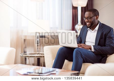 I have to work. Delighted young afro American man using his laptop in a hotel room after meeting
