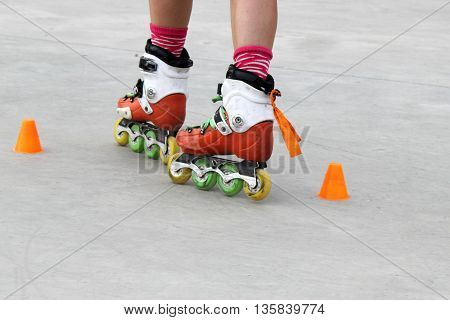 girl turning while skating with cones in a grey floor
