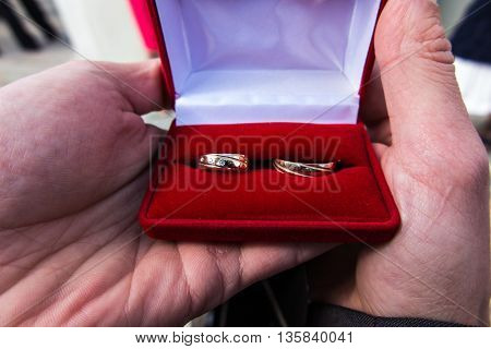 Wedding rings in a red box held in his hands