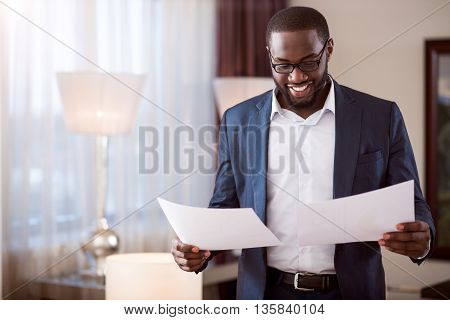 Lets analyze it. Handsome delighted afro American man standing and holding papers while looking at them with satisfaction