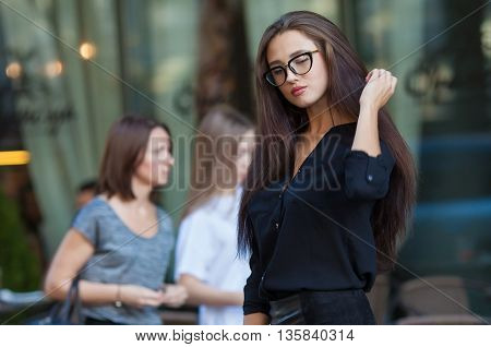 Portrait Of Young Beautiful Woman. beautiful young brunette fashion model posing outdoor. Summer outdoor portrait. Focus on woman, blurred background.