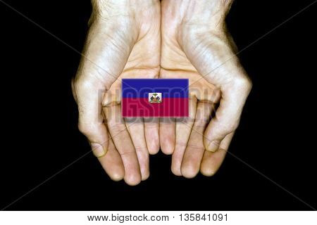 Flag Of Haiti In Hands On Black Background