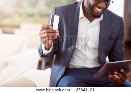 New way of payment. Close up of a bank card holding by a cheerful successful afro American man, who looking at the screen of a tablet while sitting