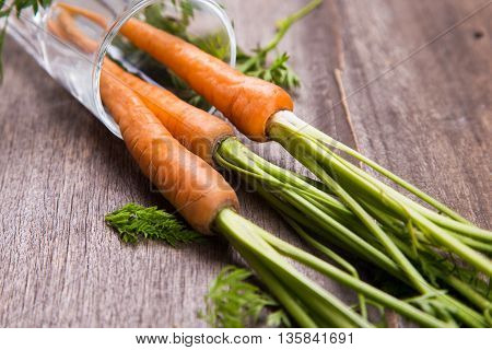 ripe fresh raw carrot with leaf on wooden background