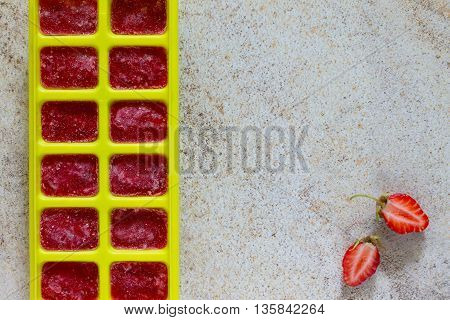 Ice Made From Strawberries For Summer Drinks With Copy Space On Brown Stone Background.