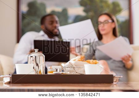 So delicious. Close up of a tray with some food and coffee with man and woman working on the back ground