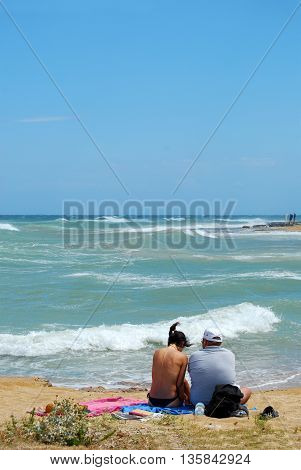 A couple of tourists on the beach swept by the Mistral in Apulia - Italy