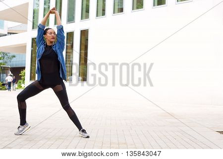 young woman dancing in the street with copyspace