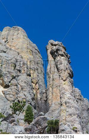 A granite column reaches towards a blue sky.