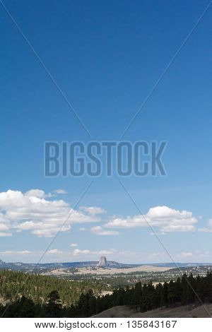 White fluffy clouds float over Devil's Tower under a blue sky.