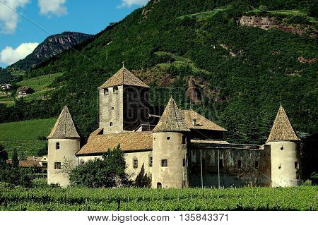 Bolzano, Italy - June 2, 2010: The feudal Castello Mareccio with its enclosure defense wall three round towers capped with conical roofs and giant keep surrounded by Tyrolean vineyards
