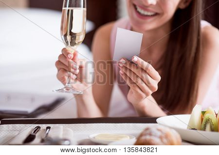 Amazing morning. Close up of hands of a woman holding a business card and a glass of champagne while lying on the bed in a hotel room