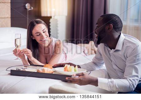 Nice of him. Afro American smiling man putting a tray with breakfast on the bed while looking at the woman lying on it with a glass of champagne