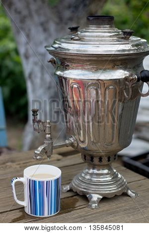 Traditional Russian Tea From An Old Samovar In The Garden Outdoors In Summer