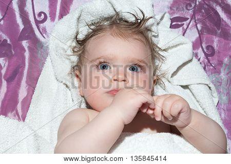 Little wet girl after bath on the blanket