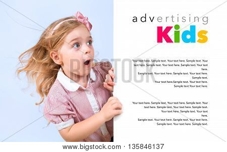 little astonished girl appears behind white banner