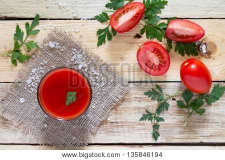 Glass Of Tomato Juice With Green Leaves On A Wooden Background, Top View.