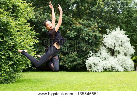 A Jazz dancer performing a jump outdoors