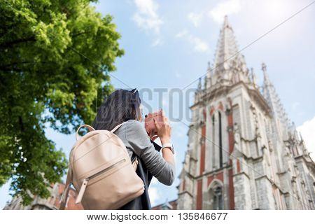 Memory storage. Pleasant beautiful woman holding camera and taking photos while having a walk