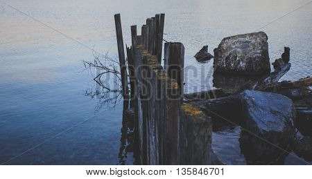 Weathered and broken boat dock on a lake.
