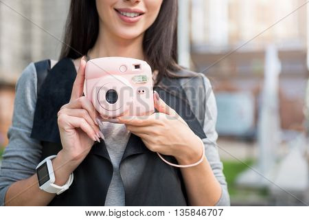 My little storage. Positive delighted beautiful woman smiling and holding photo camera while having a walk