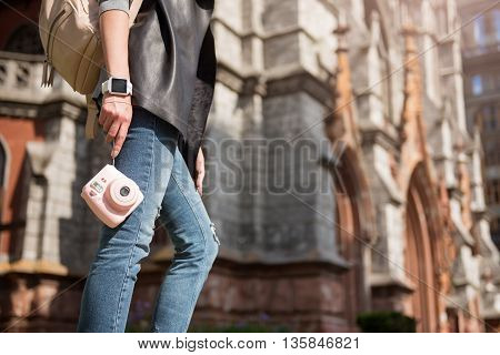Modern tourist. Pleasant woman holding photo camera and having a walk while standing in the street
