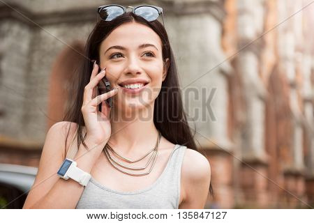 Ready to receive calls. Pleasant beautiful smiling woman holding cellphone and talking while standing in the street
