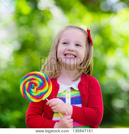 Cute little girl with big colorful lollipop. Child eating sweet candy bar. Sweets for young kids. Summer outdoor fun. Preschooler kid with sugar lolly. Children having snack in a park after preschool.