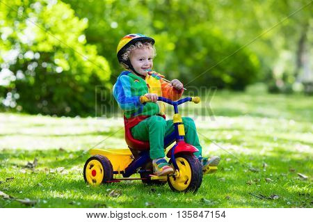 Cute boy wearing safety helmet riding his tricycle in sunny summer park. Kids ride bicycle. First bike for little child. Active toddler kid playing and cycling outdoors. Kids play in the garden.