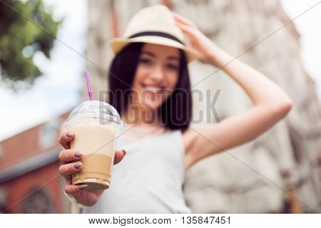 Take it away. Close up of cocktail in hand of pleasant cheerful woman holding it and giving to you while having a walk