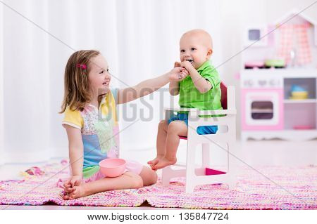 Cute little girl feeding baby brother in a white play room. Kids playing with toy dishes and kitchen. Little boy in high chair during lunch or breakfast with his big sister. Nutrition for children.