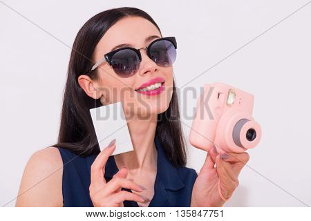 Pleasant look. Nice delighted smiling beautiful smiling woman holding photo and camera while standing isolated on white background